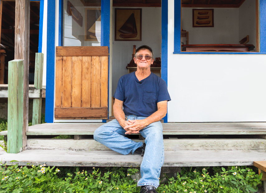 Andy Albury sitting in front of his home